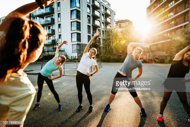 urban fitness group warming up for run - sportkleding stock pictures, royalty-free photos & images