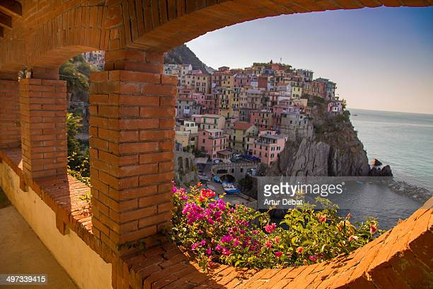 Urban garden in window with the town of Manarola in Cinque Terre Italy