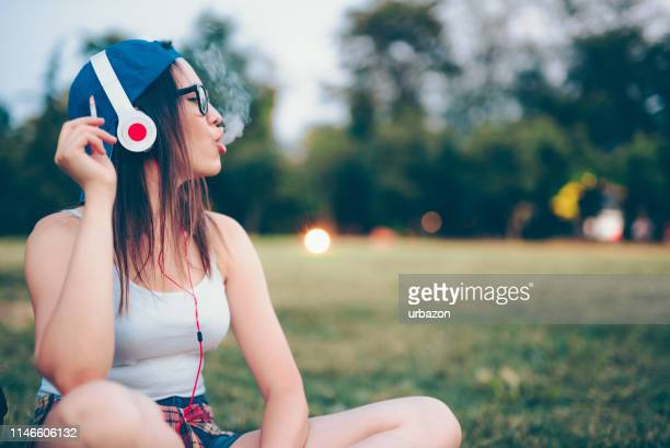 urban girl smoking and listening to music - beautiful women smoking cigarettes stock pictures, royalty-free photos & images