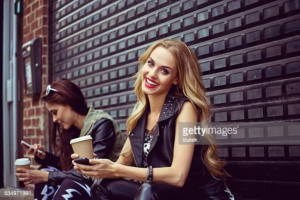 urban girls using smart phones - izusek stock photos and pictures