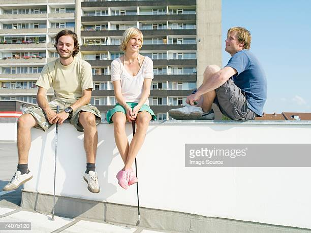 Urban golfers sitting on wall