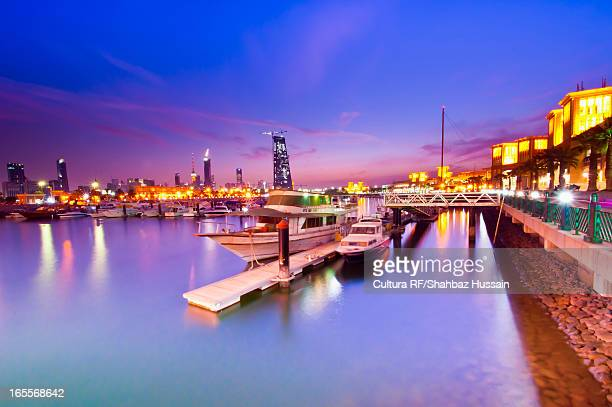 urban harbor lit up at night - kuwait city stock photos and pictures