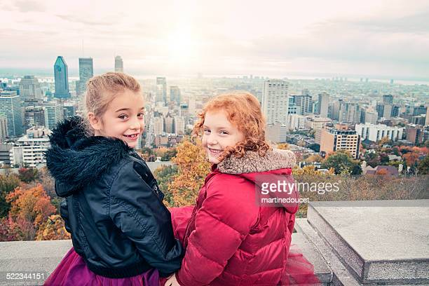 Urban kids: two little girls sitting in front of cityscape.