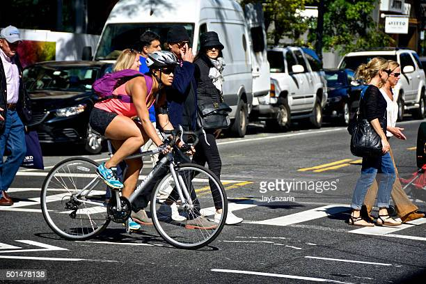 urban life, new york city, female bicyclist at manhattan intersection - pedestrians stock photos and pictures