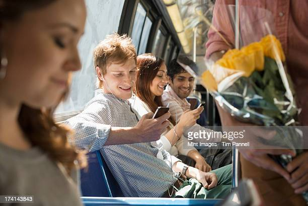 Urban Lifestyle. A group of people, men and women on a city bus, in New York city. Two people checking their smart phones.