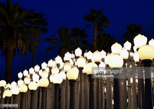 """Urban Light"""" by artist Chris Burden illuminates amber hue at LACMA to support the Biden Inaugural Committee's COVID-19 Memorial: A National Moment of..."""