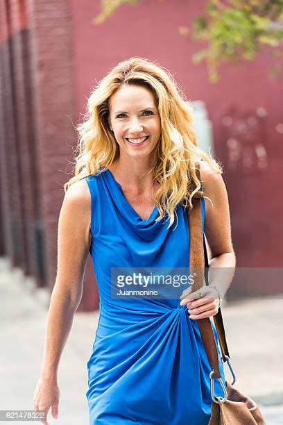 urban mature blond woman - long purse stock photos and pictures