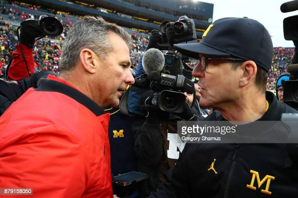 Urban Meyer head coach of the Ohio State Buckeyes and Jim Harbaugh head coach of the Michigan Wolverines shake hands after the game Ohio State won 31...