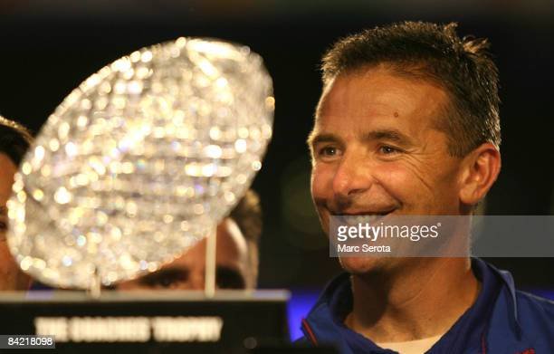 Urban Meyer of the Florida Gators smiles as he is presented with the National Championship trophy after their 24-14 win against the Oklahoma Sooners...
