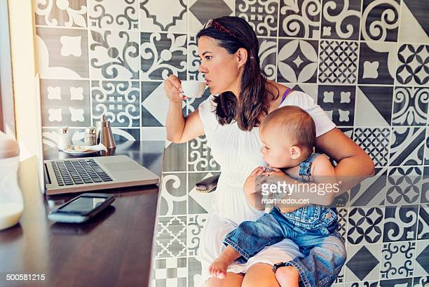 urban mom balancing work and family in a public cafe. - pregnant coffee stock pictures, royalty-free photos & images