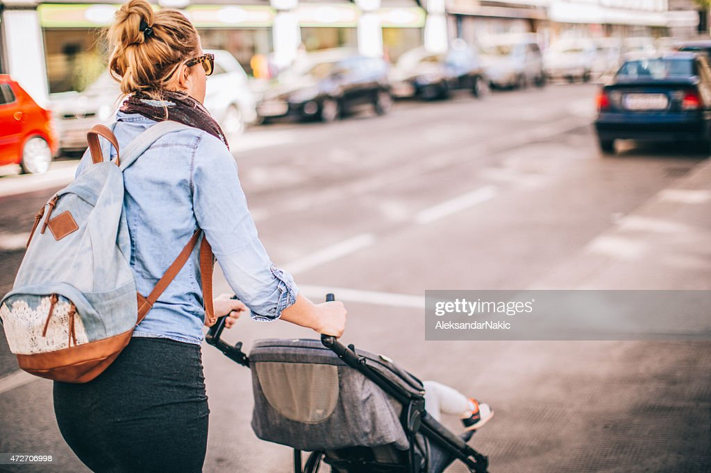 Urban mom with a buggy : Stock Photo