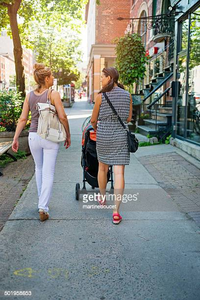 Urban mom with stroller walking down the street with friend.