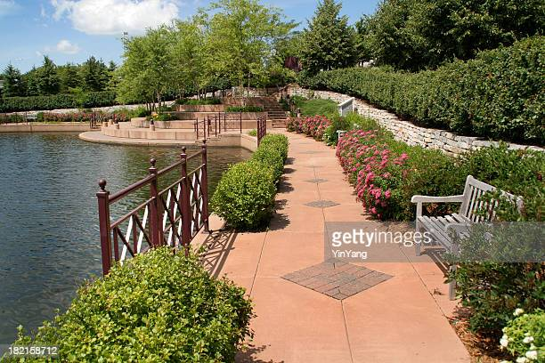 urban park with walking path, landscaping by lake in spring - minnesota bildbanksfoton och bilder