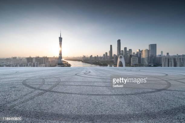 urban parking lot against city skyline, during sunset - guangzhou stock-fotos und bilder