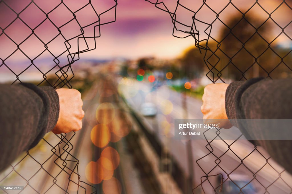 Urban picture taking from personal perspective of guy opening grid fence. : Stock Photo