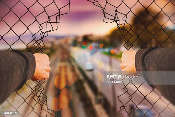 urban picture taking from personal perspective of guy opening grid fence. - 境界 ストックフォトと画像
