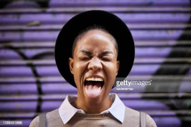 ritratto urbano di donna nera espressiva che fa un volto - fare le boccacce foto e immagini stock
