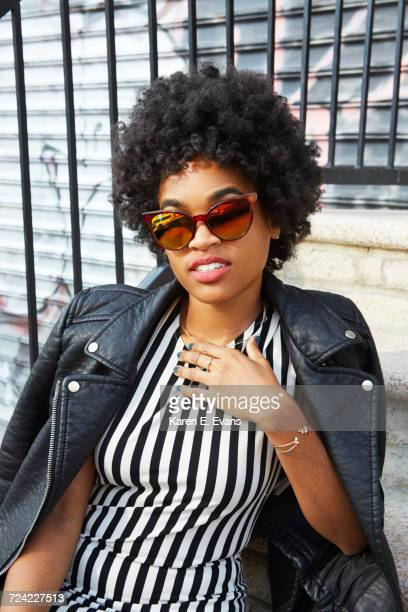 Urban portrait of young female fashion blogger with afro hair and sunglasses, New York, USA