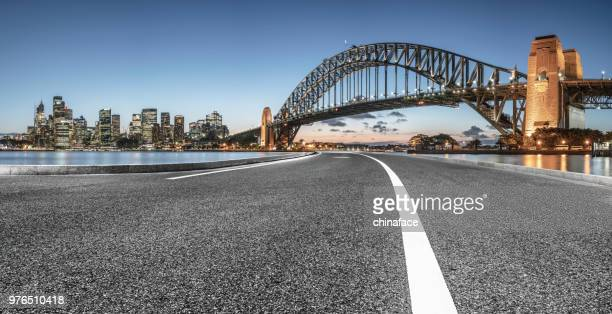 urban road by sydney harbor bridge - international landmark stock pictures, royalty-free photos & images