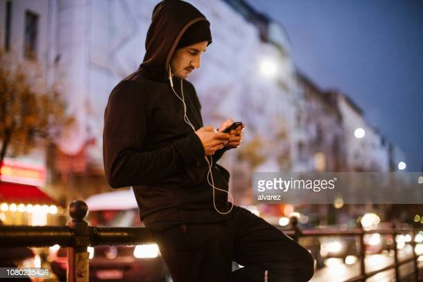 urban runner relaxing after exercising - hoodie headphones stock pictures, royalty-free photos & images