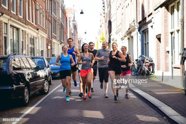 urban runners crew training in the city - running stock pictures, royalty-free photos & images