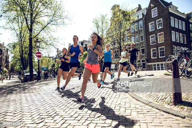 urban runners crew training in the city - sports team event stock photos and pictures