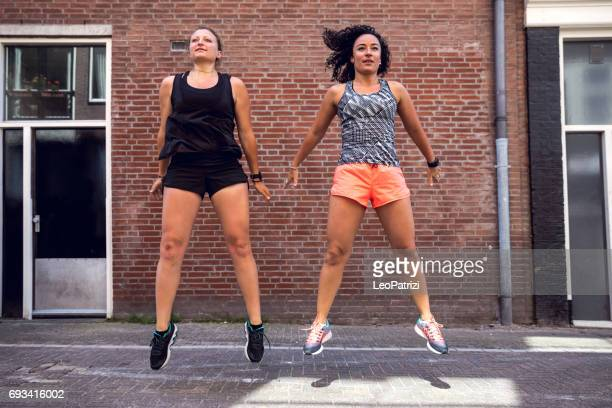 urban runners crew training in the city - squatting position stock pictures, royalty-free photos & images