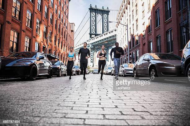 urban runners running in dumbo - new york streets - dumbo stock photos and pictures