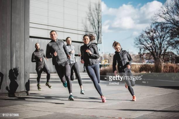 stadtlauf team - rennen körperliche aktivität stock-fotos und bilder
