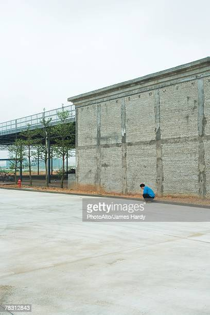 Urban scene, person crouching next to edge of building
