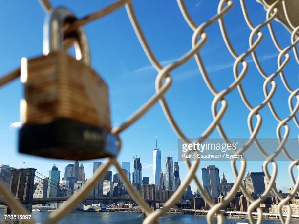 urban skyline against sky seen through chainlink fence - lower east side manhattan stock pictures, royalty-free photos & images