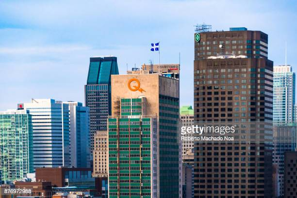 Urban skyline closeup in the daytime The Hydro Quebec and the Desjardins buildings are prominent There is a Quebec flag waving in the air