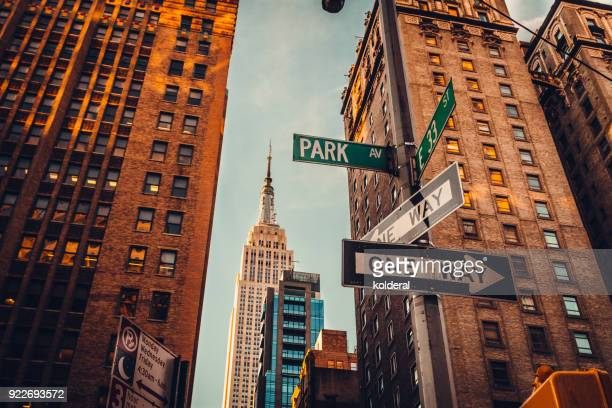 urban skyline in midtown manhattan with distant view of empire state building - new york city stockfoto's en -beelden