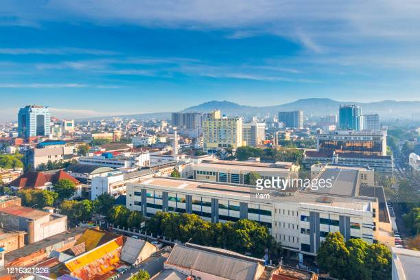 urban skyline of the densely populated bandung city in java island, indonesia, against a blue sky. - bandung stock pictures, royalty-free photos & images