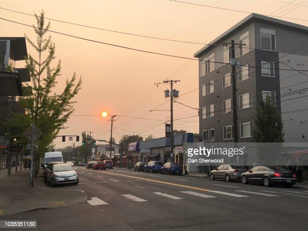 urban street and setting sun through smoky skies - dan sherwood photography stock pictures, royalty-free photos & images