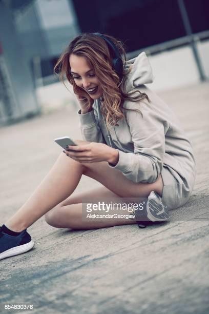 Urban Street-Style weibliche lesen SMS beim hören Musik über Kopfhörer in Stadtstraße