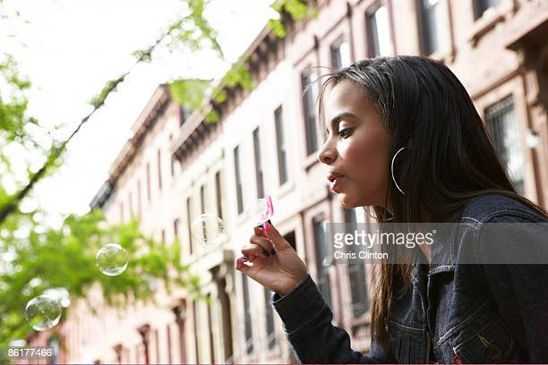 Urban teen blowing soap bubbles outside row-houses