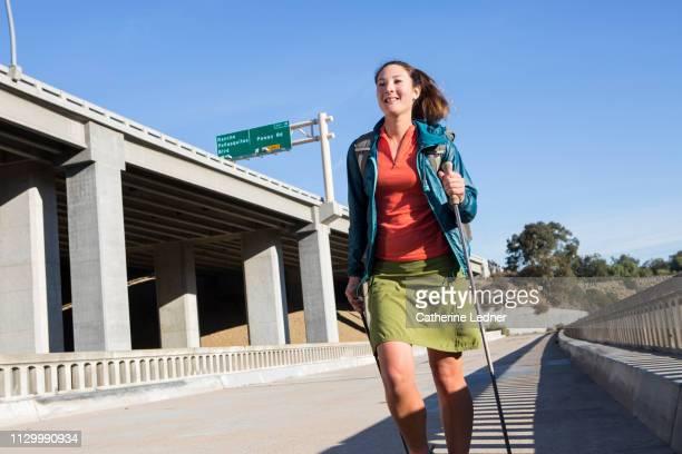 Urban walker crossing footbridge with freeway in the background
