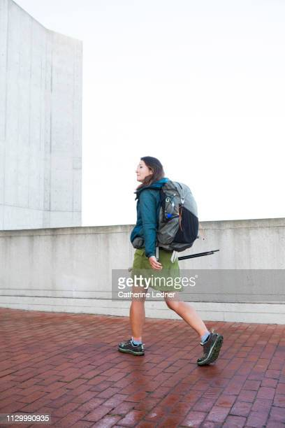 Urban walker woman with backpack and walking sticks