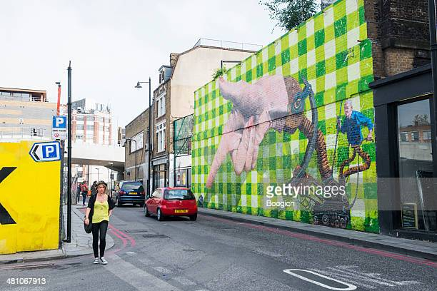 urban woman walks in east london by graffiti mural - shoreditch stock photos and pictures