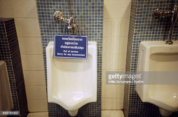Urinal Of Public Restroom With Information Sign