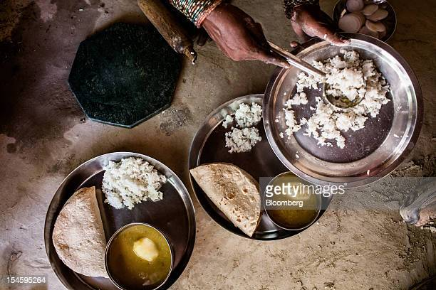 Urmila Devi serves roti rice and lentils with unripe mango on plates in Auar village in the Pratapgarh district of Uttar Pradesh India on Sunday July...