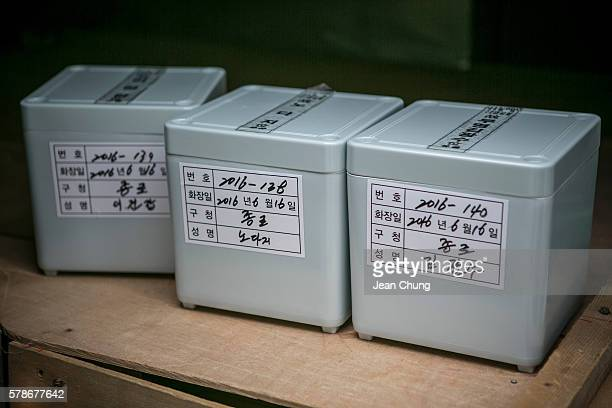 Urns that hold remains of three men who died lonely are placed inside a minivan before being taken to a charnel house on June 16 2016 in Goyang South...