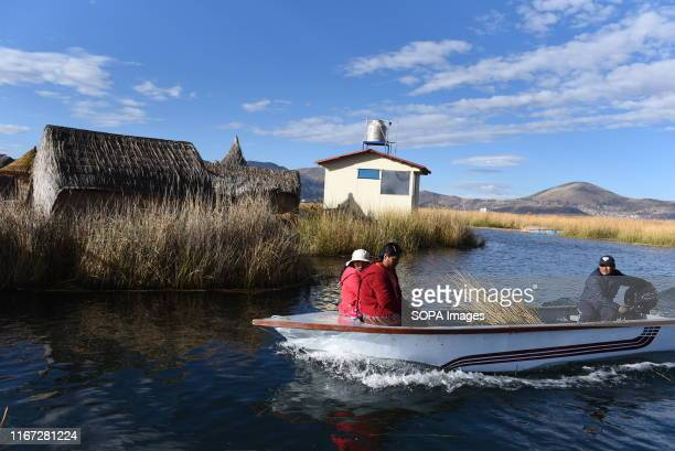 Uro family on board a motor boat sailing among the totora reed in Titicaca lake The Uru or Uros are indigenous people of Peru and Bolivia who live on...