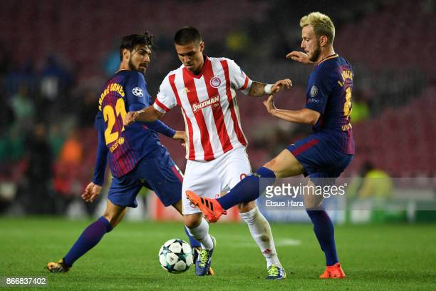 Uros Djurdjevic of Olympiakos competes for the ball against Andre Gomes and Ivan Rakitic of Barcelona during the UEFA Champions League group D match...