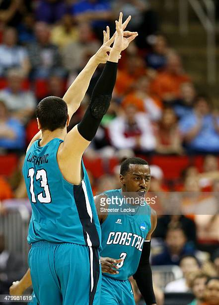 Uros Ljeskovic and Josh Cameron of the Coastal Carolina Chanticleers celebrate a threepointer in the first half against the Virginia Cavaliers during...