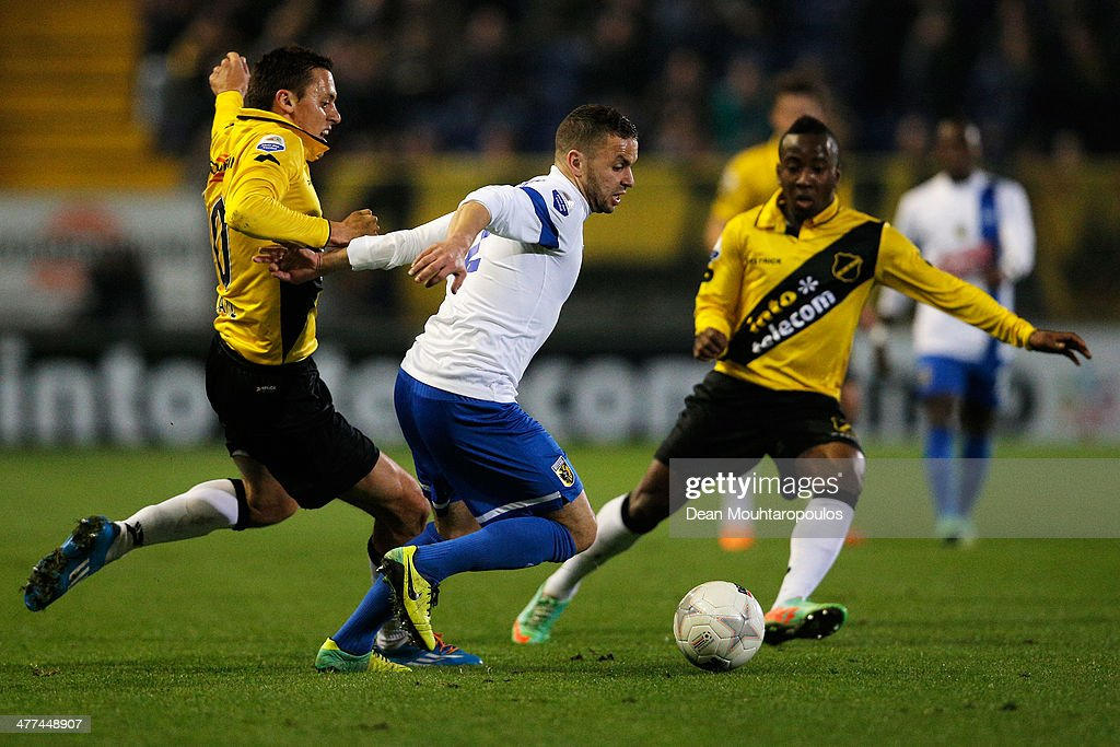 Uros Matic (L) and Elson Hooi (R) of NAC tackle Rochdi Achenteh of Vitesse during the Eredivisie match between NAC Breda and Vitesse at the Rat Verlegh Stadion on March 8, 2014 in Breda, Netherlands.