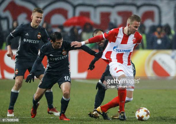 Uros Racic of Crvena Zvezda is challenged by Alan Dzagoev of CSKA Moscow during UEFA Europa League Round of 32 match between Crvena Zvezda Belgrade...