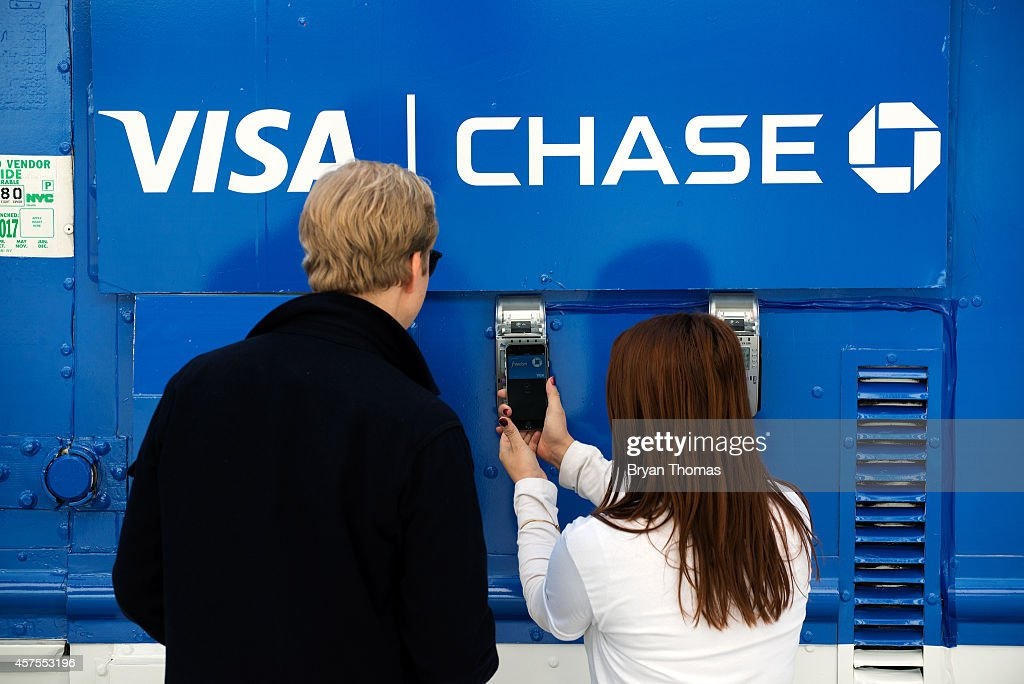 Ursula Anderman (right) teaches a New York pedestrian how to use Apple Pay, as part of a Visa/Chase promotion, on October 20, 2014 in New York, NY. The software, which debuted today, is available in the recently updated iPhone 6 software and accepted in 220,000 stores. It allows iPhone users to pay for purchases using their iPhone's NFC capabilities instead of using their credit card.