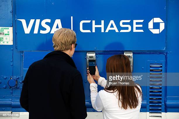 Ursula Anderman teaches a New York pedestrian how to use Apple Pay as part of a Visa/Chase promotion on October 20 2014 in New York NY The software...